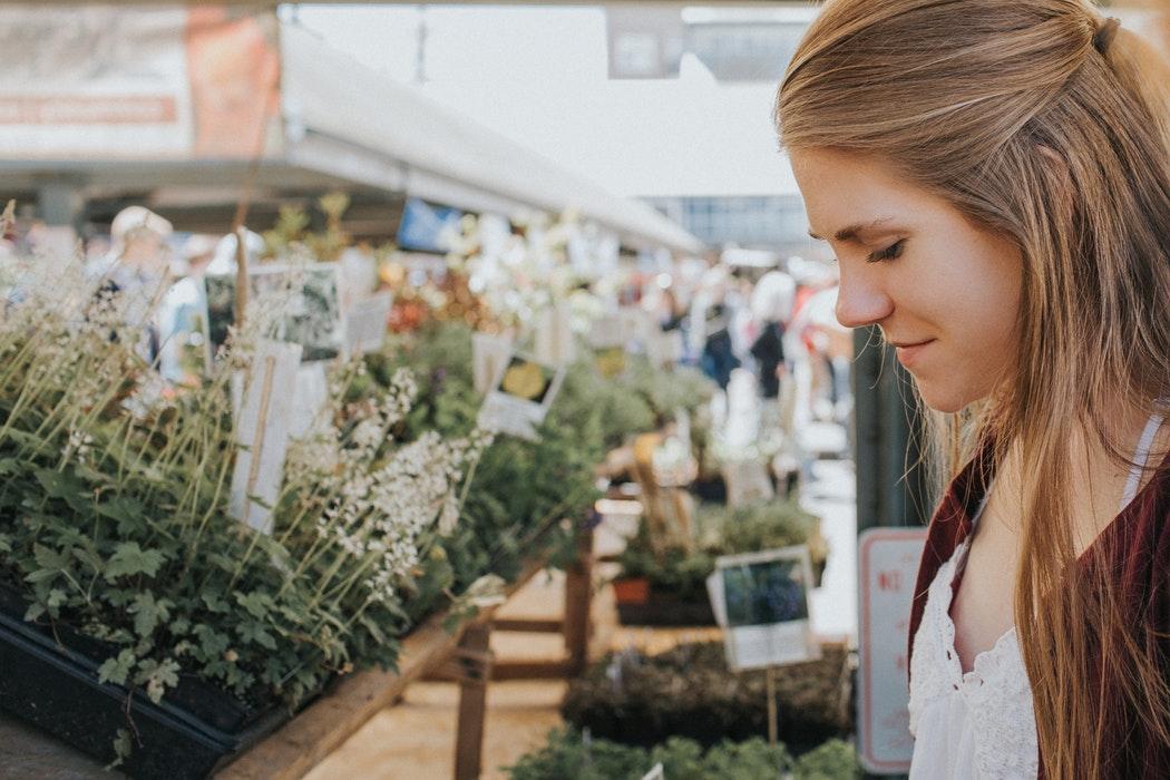 Kobieta spogląda na kwiaty na stoisku /Choroby alergiczne. Reakcje alergiczne: typy, objawy