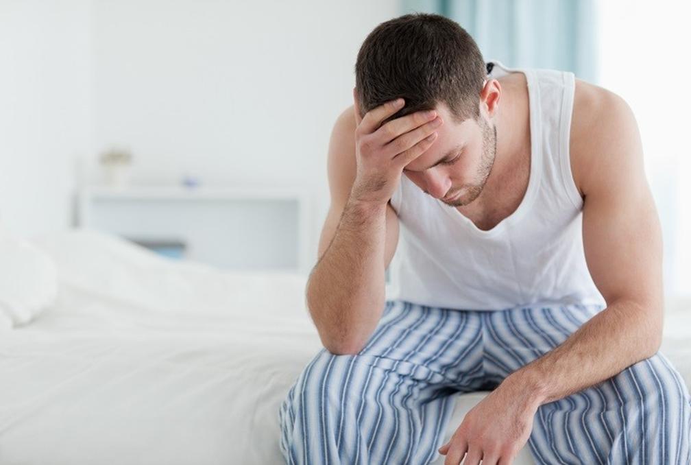 Zmartwiony mężczyzna siedzi w piżamie na brzegu łóżka /Ilustracja do tekstu: Przyczyny nieprawidłowych wyników badania nasienia