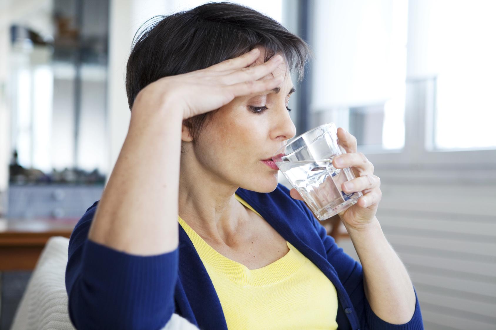 Kobieta zmagająca się z uderzeniami gorąca pije wodę /Menopauza i uderzenia gorąca: Jak z nimi walczyć