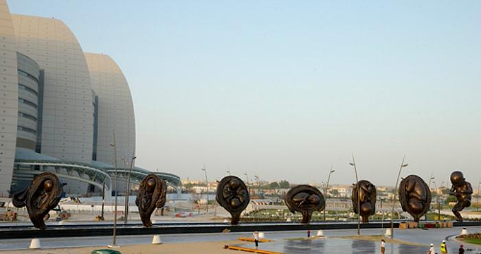 """Zdjęcie przedstawiające wystawę """"Cudowna podróż"""" Damiena Hirsta na tle budynku szpitala w Doha (Katar)"""