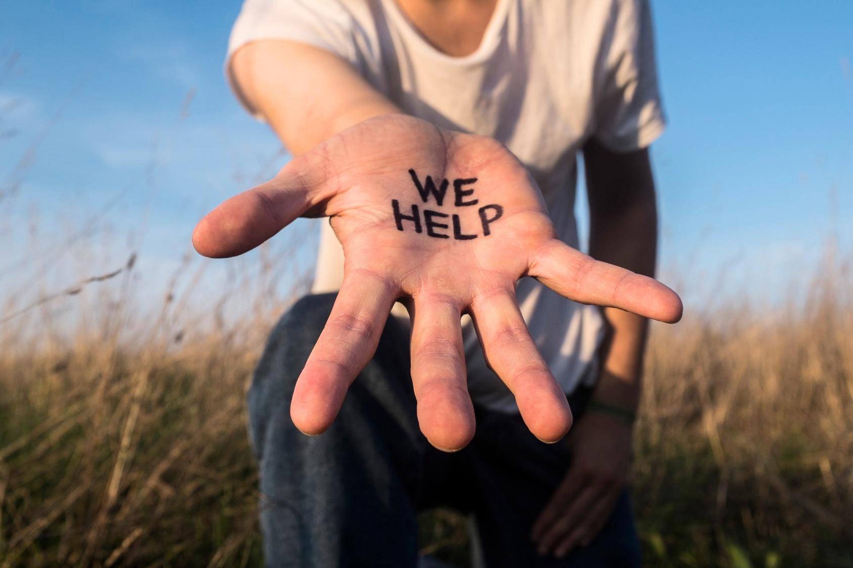 """Wyciągnięta dłoń; na niej napis: We help [Pomagamy] /Ilustracja do tekstu: Projekt """"Bezpestkowe"""", czyli wsparcie w drodze do akceptacji MRKH"""