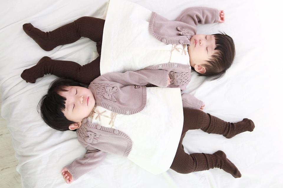 Roczne bliźniaczki leżące obok siebie w identycznych strojach /Ilustracja do tekstu: Pierwsze zmodyfikowane genetycznie bliźnięta odporne na HIV. Przyszły na świat w Chinach